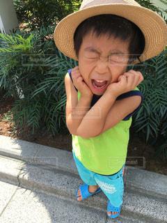 夏の暑い日、麦わら帽子を被った少年の写真・画像素材[1420969]