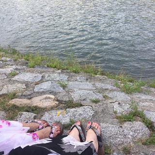 水の体の真ん中に岩の上に座っている人の写真・画像素材[1416905]