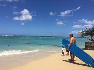 ビーチでサーフボードを運ぶ男の写真・画像素材[1416907]