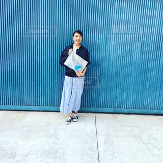 青い壁の前に立っている人の写真・画像素材[1432201]