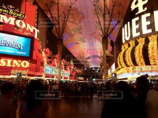 バック グラウンドでフレモント ストリート エクスペリエンスと店の前を歩く人々 のグループの写真・画像素材[1430902]