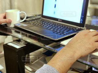 テーブルの上に座っているラップトップ コンピューターを使用している人の写真・画像素材[1793250]