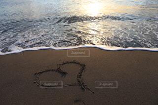 波打ち際、砂に書いたハートの写真・画像素材[3879937]
