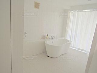シャワーの横に座っている白い浴槽の写真・画像素材[1466309]