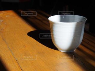木製のテーブルの上に座ってコーヒー カップの写真・画像素材[1706924]