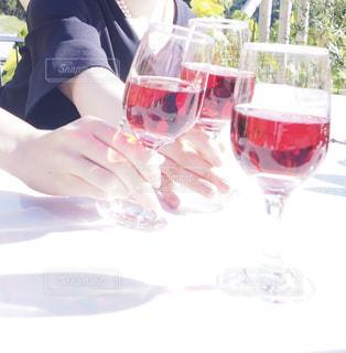 ワイングラスを持つテーブルに座っている女性の写真・画像素材[1726745]