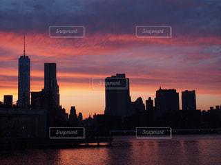バック グラウンドで市と水体に沈む夕日の写真・画像素材[1733347]