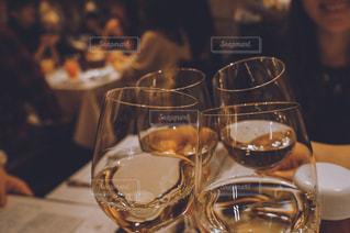 ワイングラスを持ったテーブルに座る人のクローズアップの写真・画像素材[2128619]