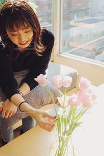 花の花瓶とテーブルに座っている女性の写真・画像素材[1821243]