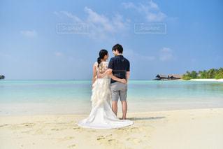 水の体の近くのビーチに立っている夫婦の写真・画像素材[1836266]