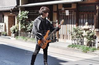 通りに立ってベースを弾く男の写真・画像素材[1849981]