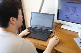 ラップトップコンピュータの前の机に座っている男の写真・画像素材[3124068]