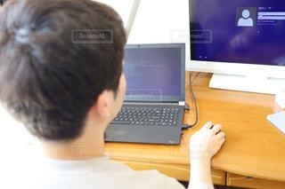 ラップトップコンピュータの前に座っている人の写真・画像素材[3124069]