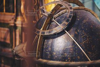 木製の椅子の上に座っている金の時計の写真・画像素材[1439764]