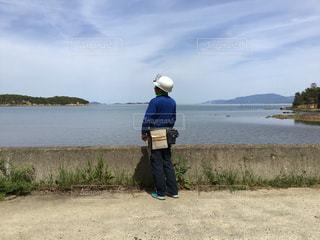 水の体の横に立っている人の写真・画像素材[1458866]