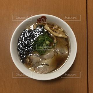 木製テーブルの上に座っているスープのボウルの写真・画像素材[1761173]