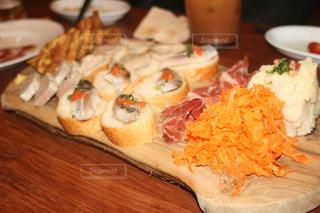 木製のまな板の上に食べ物のプレートの写真・画像素材[1443169]