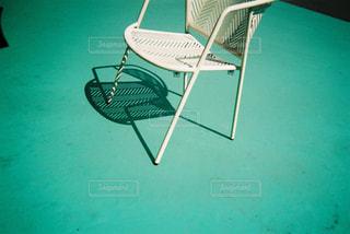 水のプールの前に座っている椅子の写真・画像素材[1443569]