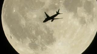 満月をバックに飛ぶ飛行機の写真・画像素材[1444730]
