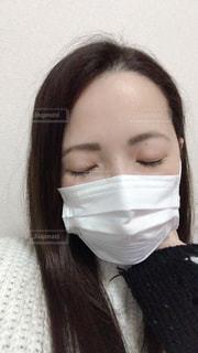 首をおさえてマスクしてる女性の写真・画像素材[1830268]