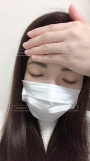おでこに手をおさえてマスクしてる女性の写真・画像素材[1830269]