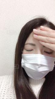 おでこに手をおさえてマスクしてる女性の写真・画像素材[1830271]