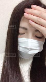 おデコに手をおさえてマスクしてる女性の写真・画像素材[1830275]