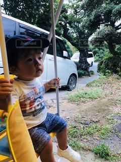 芝生に座っている小さな男の子の写真・画像素材[1449988]