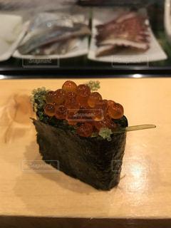 テーブルの上に寿司の上に座ってケーキの写真・画像素材[1450712]