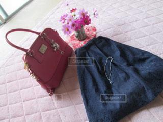 赤いハンドバッグと青のスカートの写真・画像素材[1453610]