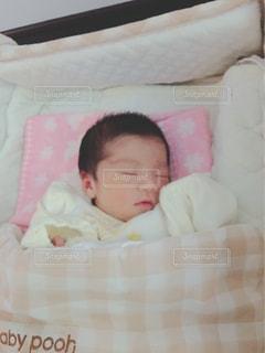 赤ちゃんのベッドの上で横になっています。の写真・画像素材[1548455]