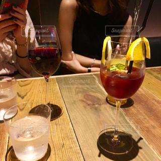 ワイングラスを持つテーブルに座っている女性の写真・画像素材[1462003]