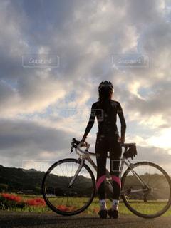 夕焼けの中のロードバイクと彼岸花と私の写真・画像素材[1494172]