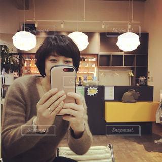 カメラにポーズ鏡の前に立っている人の写真・画像素材[1478117]