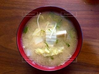 木製のテーブルの上に座っているスープのボウルの写真・画像素材[2680062]