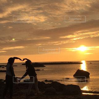 ビーチでの背景の夕日に人々 のカップルの写真・画像素材[1469778]