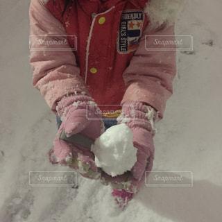 雪の中で、雪玉を持っている子供の写真・画像素材[1694342]
