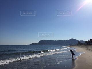 水域の隣の浜辺を歩いている人の写真・画像素材[2093863]
