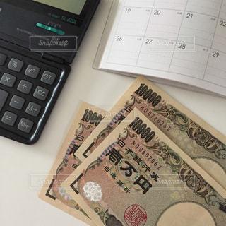 お金と電卓と手帳の写真・画像素材[2398744]