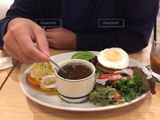 食べ物の皿を持ってテーブルに座っている人の写真・画像素材[2404896]