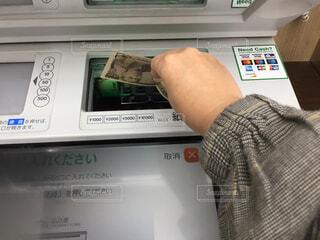 ATMと手とお金の写真・画像素材[2459489]