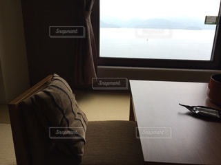窓の前にベッドと机付きのベッドルームの写真・画像素材[2468452]