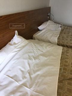 白いシーツ付きのベッドの写真・画像素材[2468455]