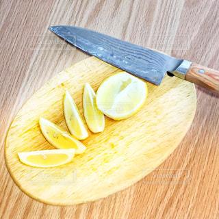 木製のまな板の上にレモンの写真・画像素材[2912972]