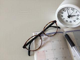 テーブルの時計 眼鏡 ペンの写真・画像素材[3156930]