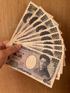 千円札を持つ手の写真・画像素材[3824701]