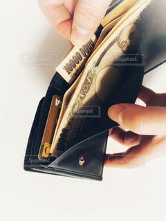 三つ折り財布とゴールドカードと現金の写真・画像素材[4170345]