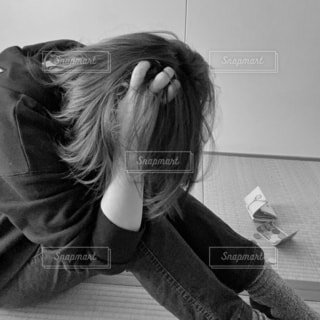 部屋でひとりうずくまる女性の写真・画像素材[4193168]