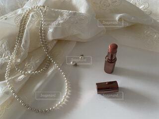 無造作に置いたドレスと口紅とパールのアクセサリーの写真・画像素材[4349726]