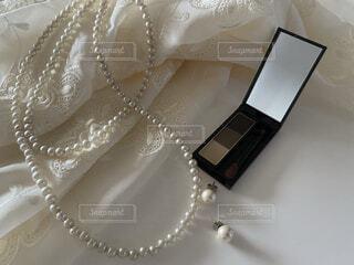 無造作に置いたドレスとアイブローパウダーとパールのアクセサリーの写真・画像素材[4349730]